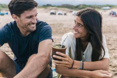 Happy young couple sharing yerba mate herbal tea at the beach.