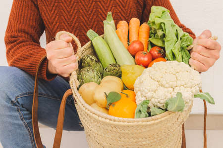 Man holding a basket full of organic veggies. Natural product concept.