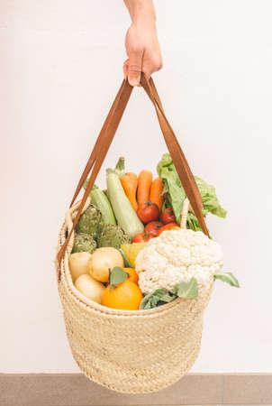 man's hand holding a wicker basket full of various seasonal vegetables