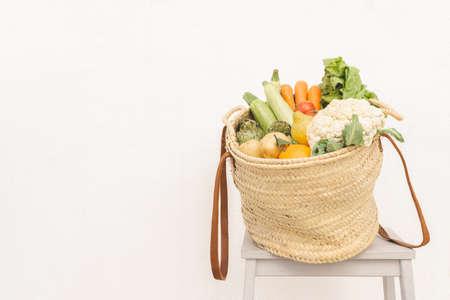 Wicker basket full of assorted vegetables against gray background. 版權商用圖片