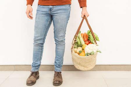 unrecognized man holding basket of assorted vegetables. Eco-friendly concept. 版權商用圖片
