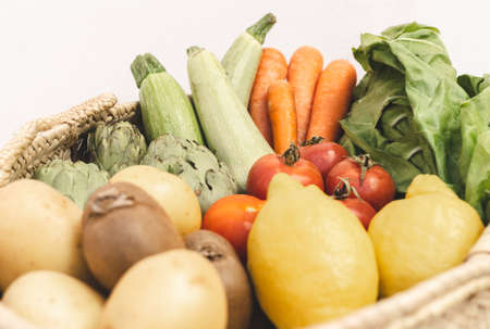 Selective focus of organic and fresh vegetables in a basket against white background. 版權商用圖片