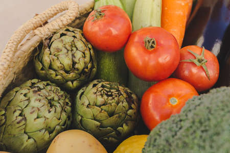 Selective focus on tomatoes and artichokes inside basket