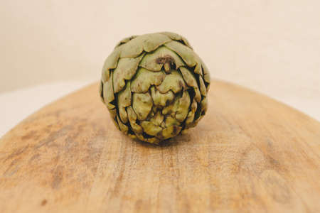 Artichoke isolated on wooden background