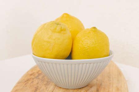 Three fresh organic lemons in a blue bowl