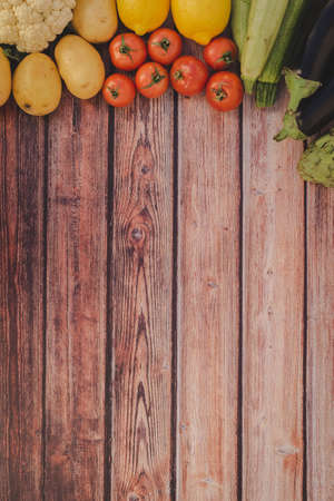 Fresh vegetables ingredients for healthy cooking on wooden background in vertical composition. 版權商用圖片