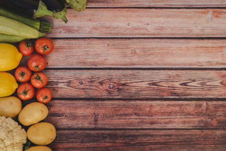 Many seasonal vegetables on wooden background with copy space.