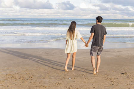 Young beautiful couple walking on the beach