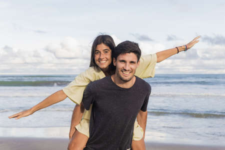 Man giving piggyback ride to his beautiful girlfriend while looking at camera with sea in background. Couple having fun at beach.