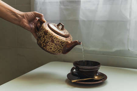 Woman pouring hot water from porcelain teapot into elegance mug with steel spoon.