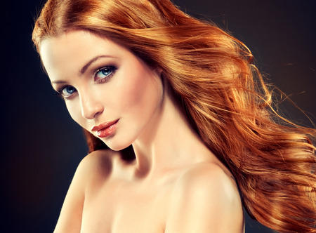 Beautiful model with long curly red hair .  Styling hairstyles curls