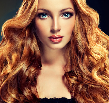 red hair beauty: Beautiful model with long curly red hair .  Styling hairstyles curls