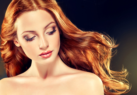 Mooi model met lang krullend rood haar. Styling kapsels krullen Stockfoto - 52325090