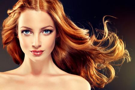 Piękny model z długimi kręconymi rudymi włosami. Stylizacja fryzury loki