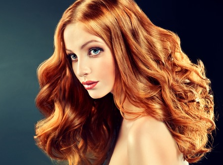 woman hairstyle: Beautiful model with long curly red hair .  Styling hairstyles curls