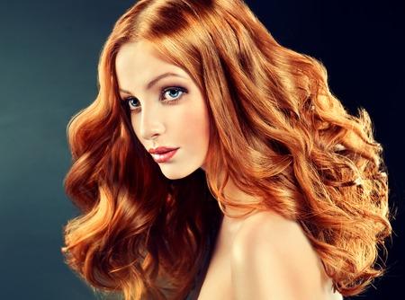 capelli lisci: Bello modello con lunghi capelli rossi ricci. acconciature Styling riccioli Archivio Fotografico