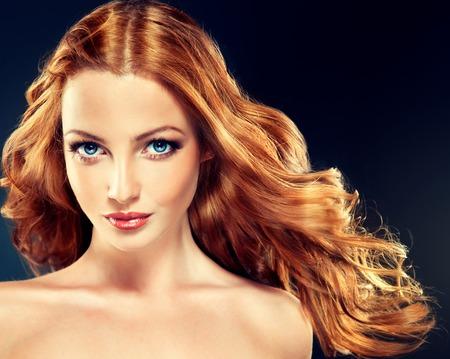 긴 곱슬 빨간 머리를 가진 아름 다운 모델입니다. 스타일링 헤어 스타일 곱슬