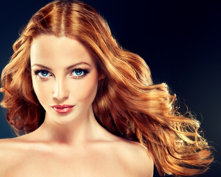 color model: Beautiful model with long curly red hair .  Styling hairstyles curls