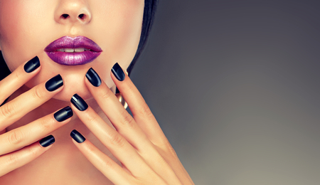polish: Beautiful girl showing black manicure nails . makeup and cosmetics