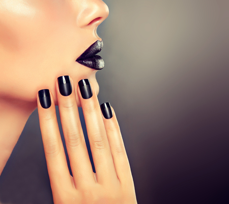 Beautiful girl showing black manicure nails . makeup and cosmetics