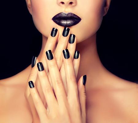 manicura: Muchacha hermosa que muestra manicura uñas negras. maquillaje y cosméticos
