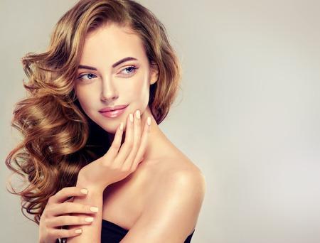 Schöne Mädchen mit langen gewellten Haaren. Brunette Modell mit dem lockigen Frisur