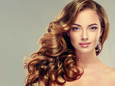 hairdressers: Beautiful girl with long wavy hair .  Brunette  model with curly hairstyle
