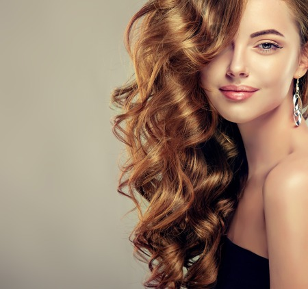 champú: Hermosa chica con el pelo largo y ondulado. Modelo morena con el peinado rizado Foto de archivo