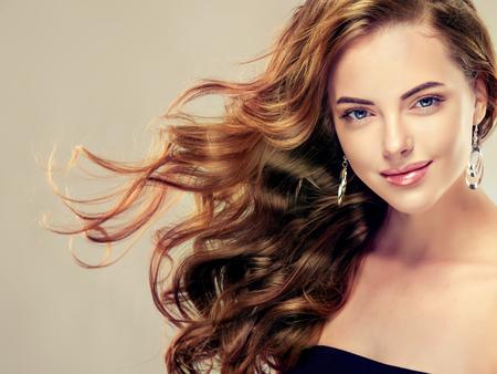 Piękna dziewczyna z długimi falującymi włosami. Model brunetka z kręconymi fryzurę Zdjęcie Seryjne
