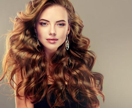長いウェーブのかかった髪を持つ美しい少女。 巻き毛のヘアスタイルとブルネットのモデル 写真素材
