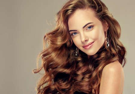 美しさ: 長いウェーブのかかった髪を持つ美しい少女。 巻き毛のヘアスタイルとブルネットのモデル 写真素材