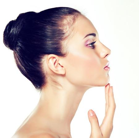 visage: Beauty Portrait. Belle Spa femme de toucher son visage. Cosmétiques et cosmétologie. Nettoyer le visage, soins de la peau. fille avec une fleur délicate près du visage