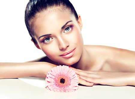 Beauty Portrait. Beautiful Spa Woman Touching her Face .  Cosmetics and cosmetology. Clean face , skin care .  girl with delicate flower near the face Stock Photo