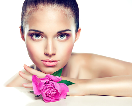 makeup beauty: Beauty Portrait. Beautiful Spa Woman Touching her Face .  Cosmetics and cosmetology. Clean face , skin care .  girl with delicate flower near the face Stock Photo