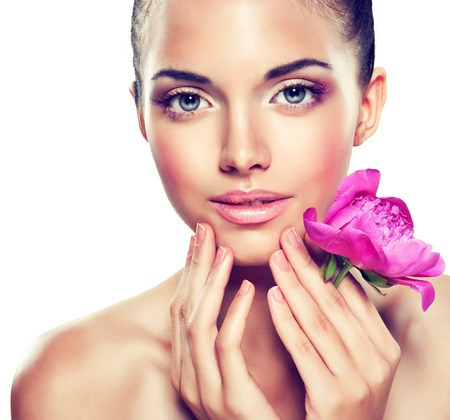 美しさの肖像画。美しいスパ女性が彼女の顔に触れます。 化粧品や美容。きれいに顔、スキンケアします。 顔に近い繊細な花を持つ少女 写真素材