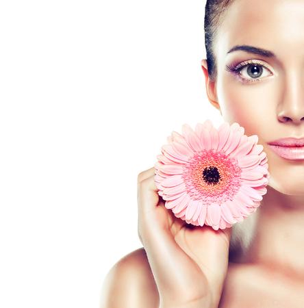 Portret Beauty. Piękna Kobieta Spa dotyka jej twarzy. Kosmetyki i kosmetologii. Czysty twarzy, pielęgnacja skóry. Dziewczyna z delikatny kwiat niedaleko twarzy