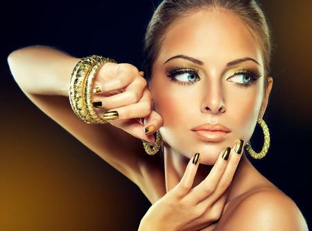 Mooi meisje met de gouden make-up en goud metalen nagels. Mode vrouw Portret