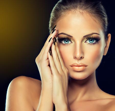 黄金化粧金の金属爪と美しい少女。 ファッション女性の肖像画