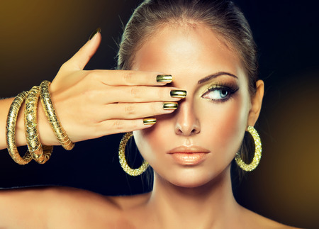 Beautiful girl with the Golden makeup and gold  metal nails.  Fashion woman Portrait.