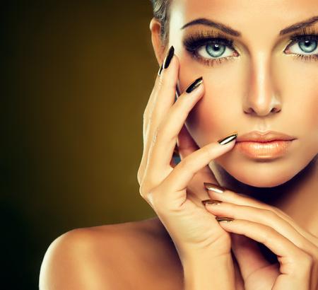 Mooi meisje met de gouden make-up en goud metalen nagels. Mode vrouw portret.