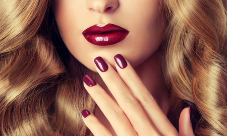 finger tip: Beautiful girl with long wavy hair .  woman with red manicure .  girl with plum color nail Polish on the nails . Stock Photo