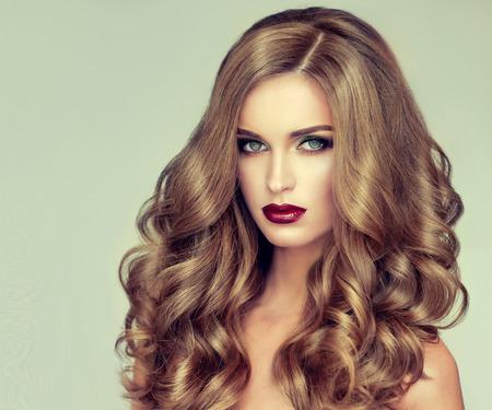 긴 물결 모양의 머리를 가진 아름 다운 소녀입니다. 곱슬 헤어 스타일과 세련된 메이크업 국방 모델입니다. 밝은 보라색 입술 스톡 콘텐츠 - 56035159