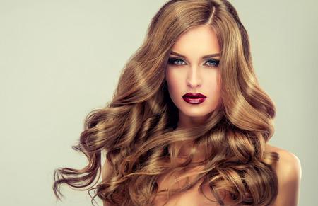 긴 물결 모양의 머리를 가진 아름 다운 소녀입니다. 곱슬 헤어 스타일과 세련된 메이크업 국방 모델입니다. 밝은 보라색 입술