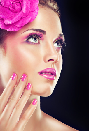 Stylish model girl with pink manicure nails and with clip on his head .