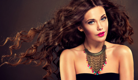 stylish hair: Beautiful model brunette with long curled hair and jewelry necklace Stock Photo