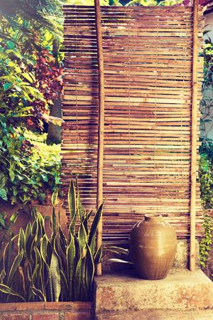 bambou: Bamboo clôture avec des plantes. plantes sur un mur de bambou.