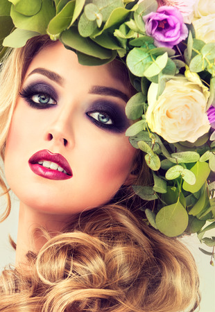 Girl spring . Beautiful model with flower wreath on his head . Makeup smoky eyes .