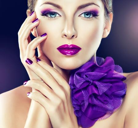 Ragazza alla moda Portrait.Violet make up e manicure. Grande arco viola sul collo. Archivio Fotografico