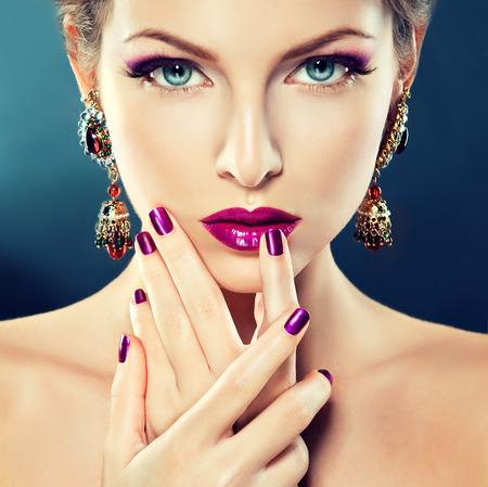 Modelo de la chica hermosa con la moda de maquillaje y manicura en las uñas de color púrpura. Joyas y cosméticos.