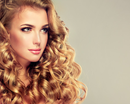 Blondel girl with long wavy hair .  Beautiful  model with curly hairstyle.